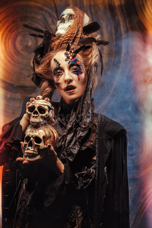 Young witch hloding skull. Bright make up and smoke- halloween theme. royalty free stock image