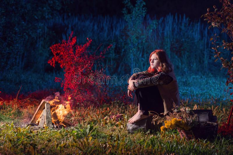 Young witch by  night fire in  forest. The young witch by  night fire in  forest royalty free stock photography