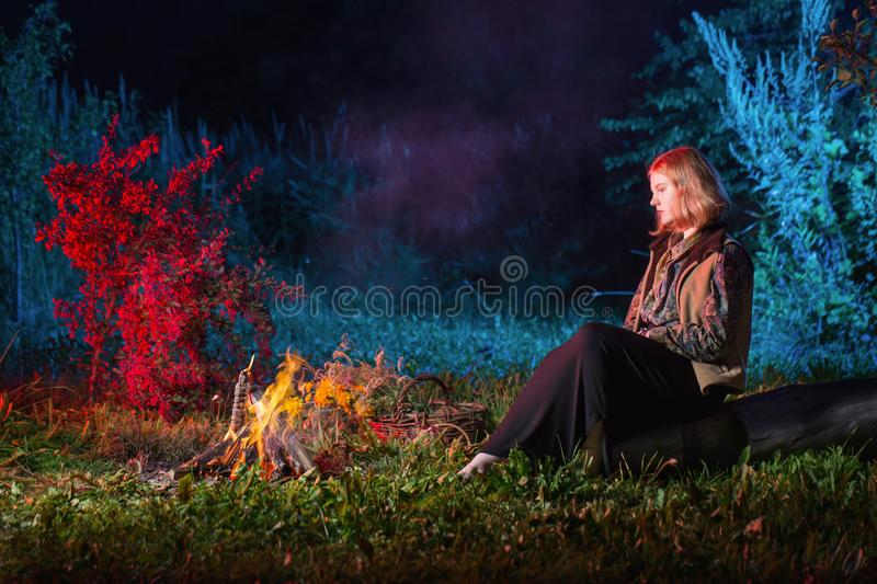 Young witch by  night fire in  forest. The young witch by  night fire in  forest stock photos