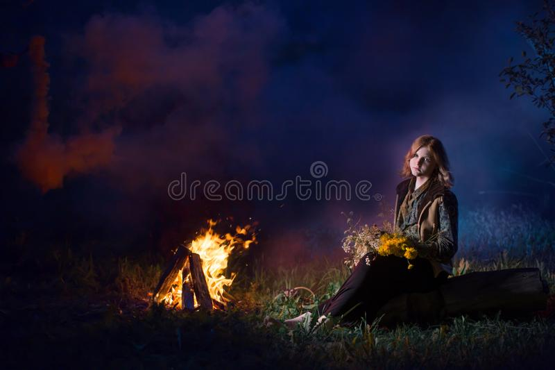 Young witch by  night fire in  forest. The young witch by  night fire in  forest stock photography