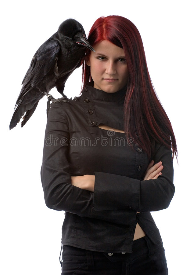 Young witch with raven. Young woman looking like a witch in black clothes with big raven on her shoulder, isolated on white