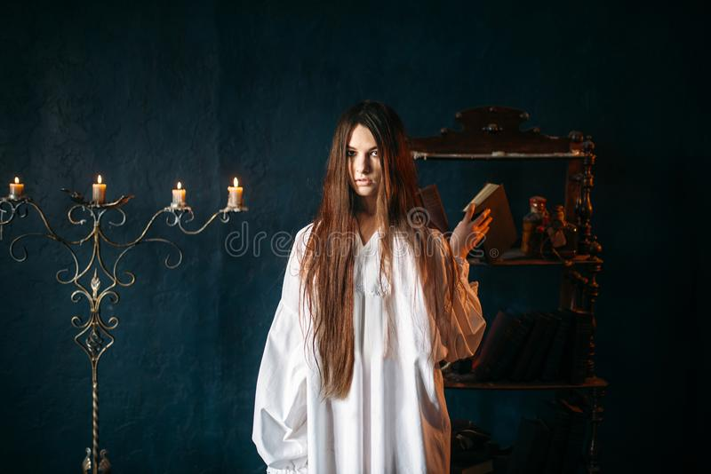 Witch holds spellbook in hands, dark magic. Young witch in white shirt holds spellbook in hands, candles on background. Dark magic ritual, occultism and exorcism royalty free stock images