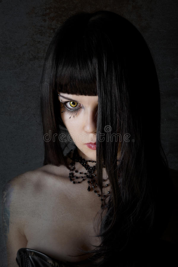 Young witch with yellow eyes royalty free stock photo