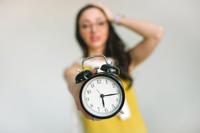 Young woaman holding alarm clock horrified about deadlines. Young woman holding alarm clock and her head horrified about deadlines royalty free stock image
