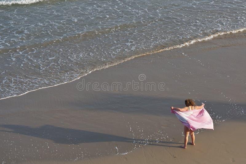 Young woaman with pink towel. Orihuela Costa, Alicante, Spain - October 21, 2018: Young woman with pink towel on sandy beach royalty free stock photos