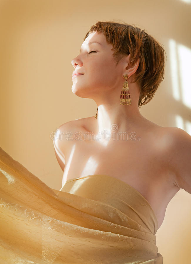 Young woman. In a interior with window shadows on the wall stock images
