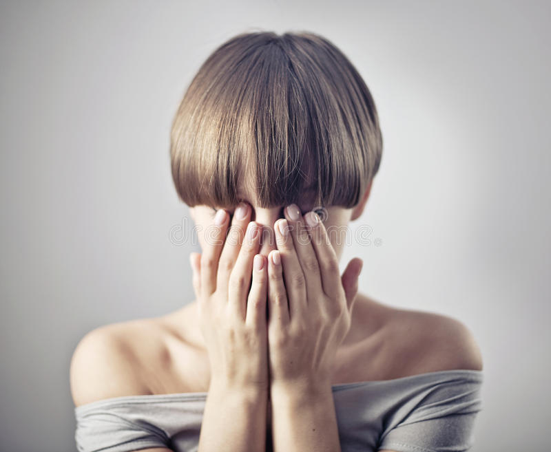 Young woman. Hide her face in her hands stock photos