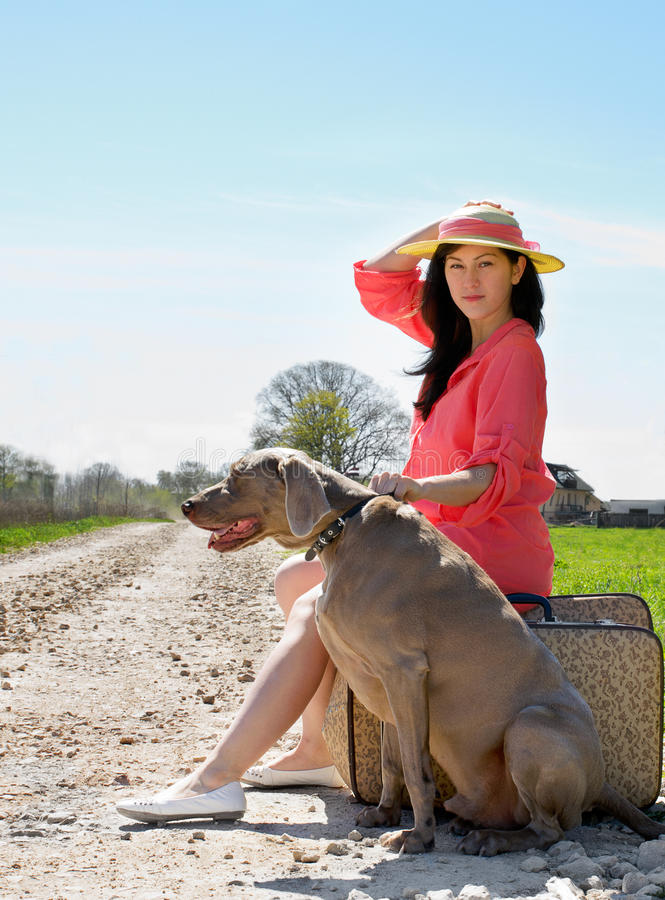 Young woman. And dog waiting on the road