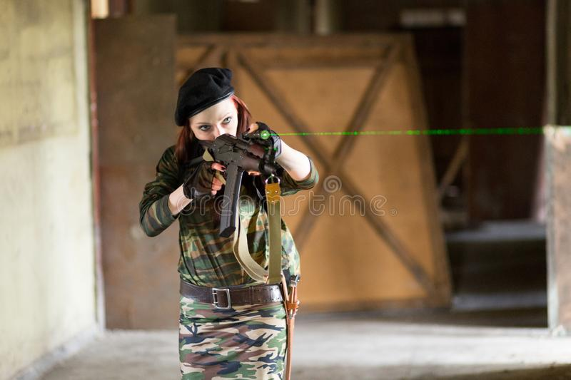 A young woman in an abandoned building with a gun. Laser sight on the machine. Aiming from the machine with a laser. The girl in stock photos