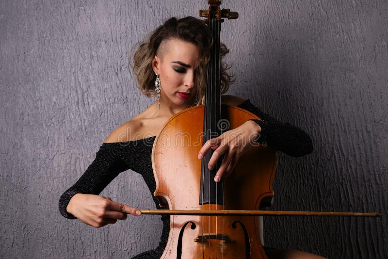Young woman with acne playing the cello royalty free stock photography
