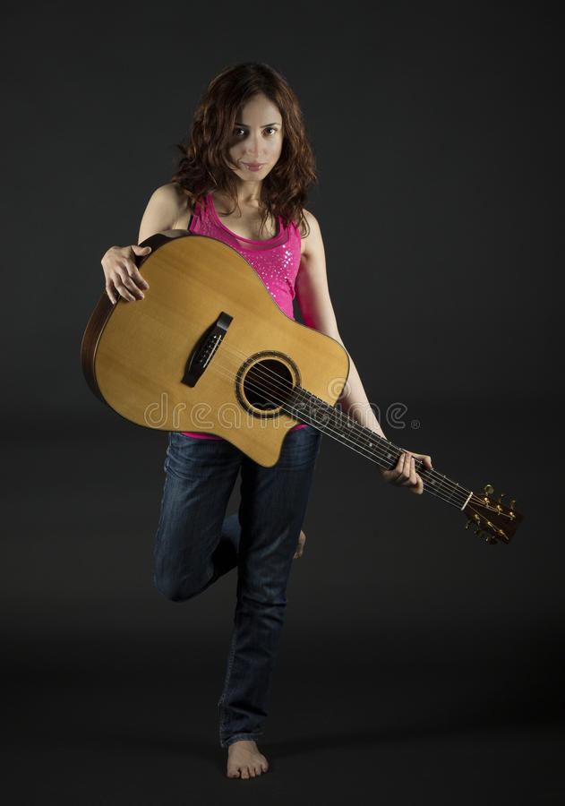 Young woman with an acoustic guitar royalty free stock images
