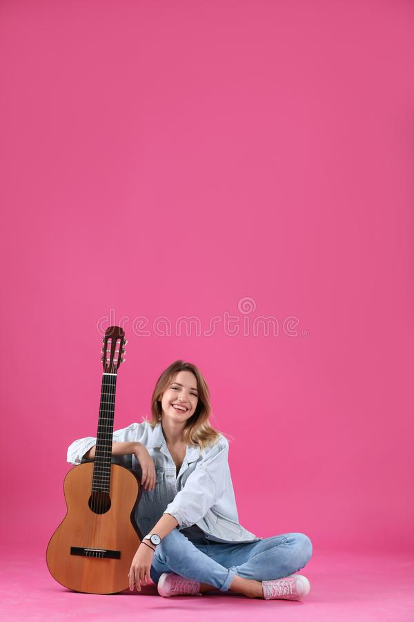 Young woman with acoustic guitar. On color background royalty free stock image