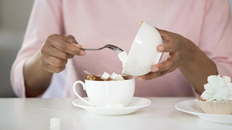Young woman adding too much sugar in tea cup, unhealthy lifestyle, diabetes. Stock photo stock photos