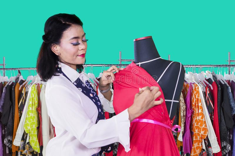 Young woman adjusting a dress on a mannequin royalty free stock photography