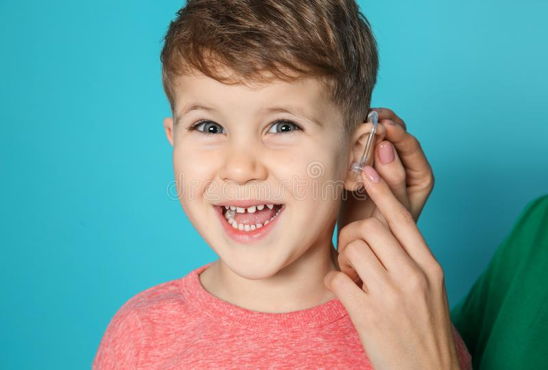 Young woman adjusting little son`s hearing aid on color background. Closeup stock photo