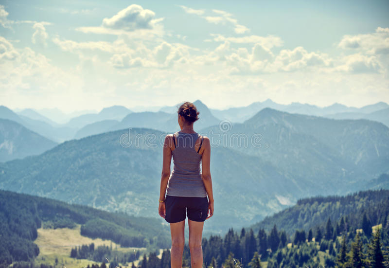 Young woman admiring a mountaintop view stock photography