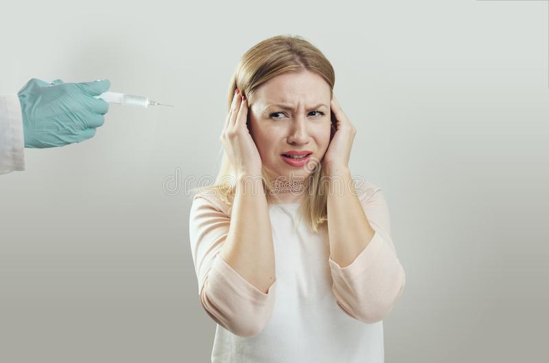 Young woman afraid of needles royalty free stock images