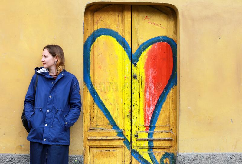 Young woman against the yellow wall and wooden doors with graffiti royalty free stock photography