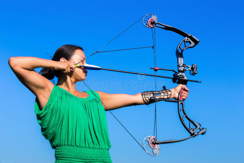 Young woman aiming arrow of compound bow. Young black haired woman aiming arrow of compound bow in blue sky royalty free stock photo