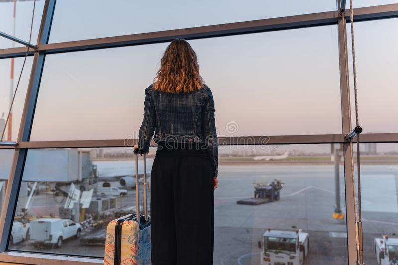 Young woman in a airport looking at the planes before departure. Woman with a trolley at the airport watching planes landing stock photos