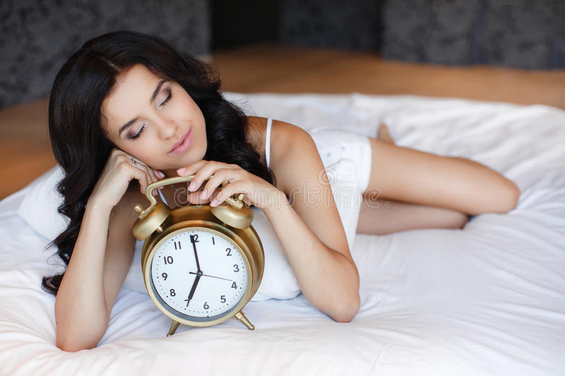 A young woman with an alarm clock in bed royalty free stock photo
