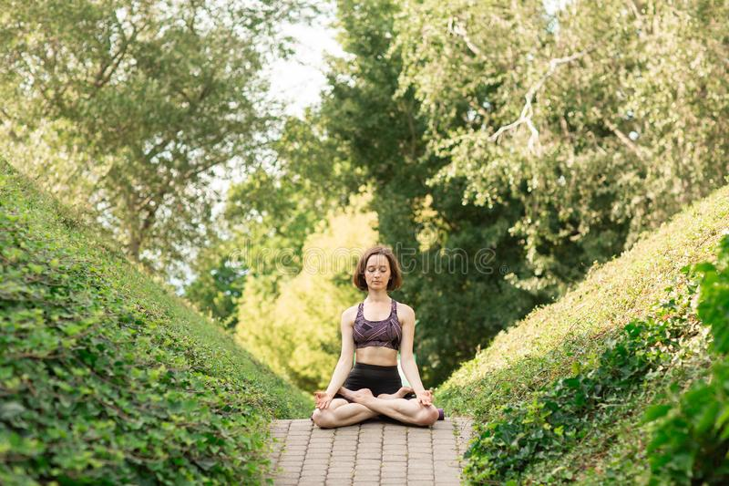 Young woman alone doing yoga on a park alley on a sunny summer day. Yoga concept stock image
