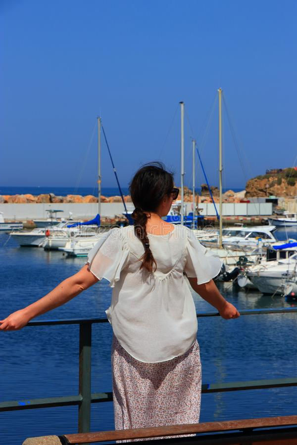 Young woman alone facing a Mediterranean port, France. Young woman alone facing a Mediterranean port, Pyrenees orientales in France royalty free stock photos