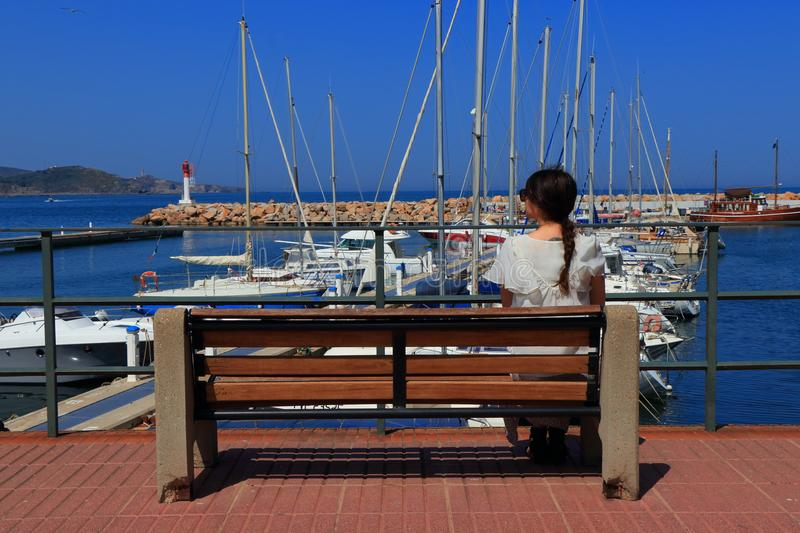 Young woman alone sitting facing a Mediterranean port. Pyrenees orientales in France royalty free stock image