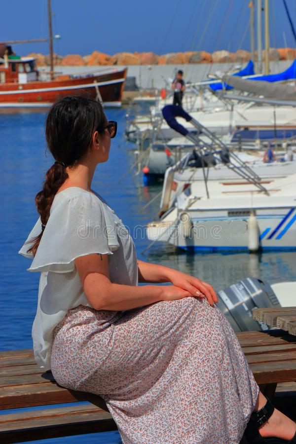 Young woman alone sitting facing a Mediterranean port. Pyrenees orientales in France royalty free stock photography