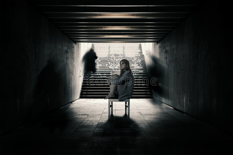 Young woman alone in a tunnel and strangers pass beyond. royalty free stock photos