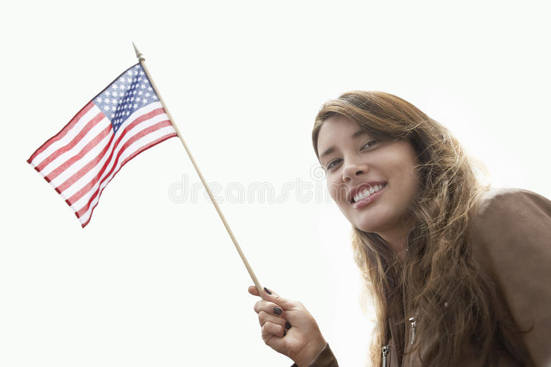 Young Woman With American Flag. Low angle view of young woman raising American flag against clear sky stock photo