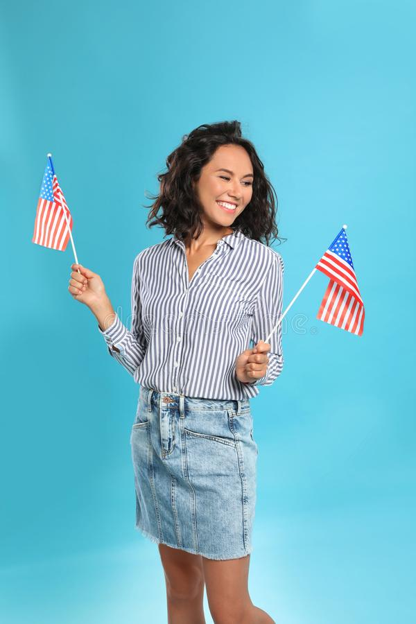 Young woman with American flags on blue background. Happy young woman with American flags on blue background royalty free stock images