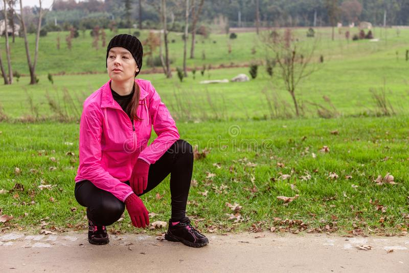 Young woman analyzing the track before running on a cold winter day on the training track of an urban park. royalty free stock photography
