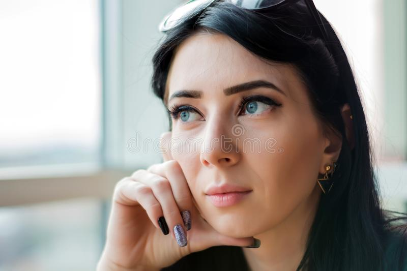 Young woman in anticipation looks out the huge window to the street.  stock images