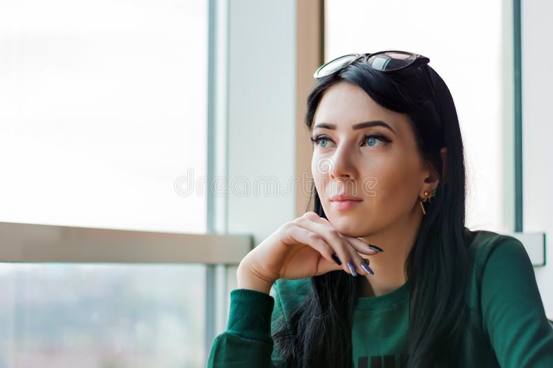 Young woman in anticipation looks out the huge window to the street.  royalty free stock photo