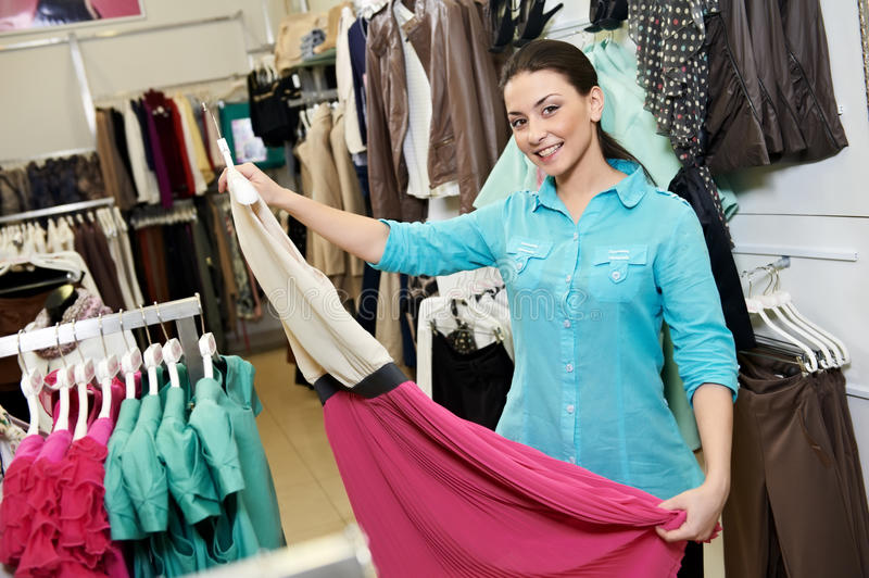 Young woman at apparel clothes shopping. Young woman choosing drerss during garments clothing shopping at store stock images