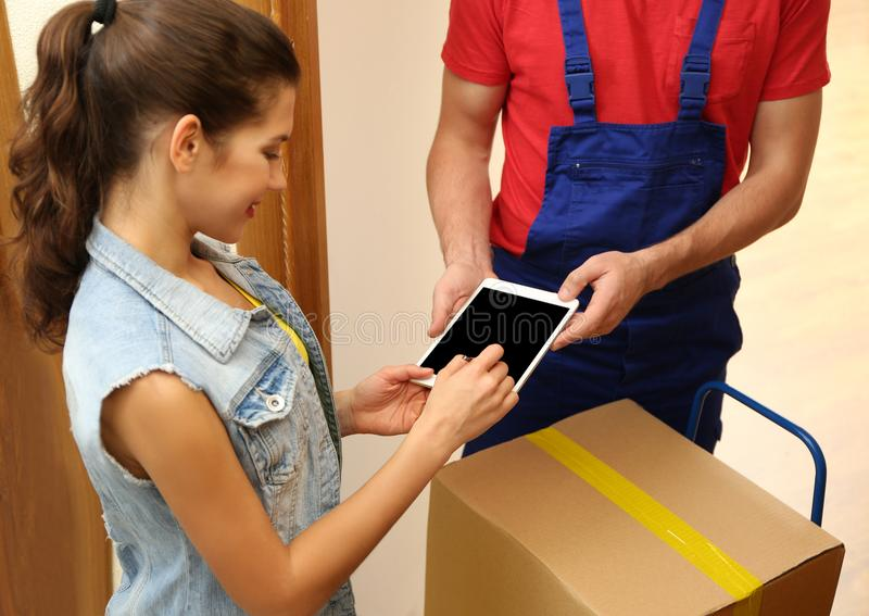 Young woman appending signature after receiving parcel. From courier at home stock photography