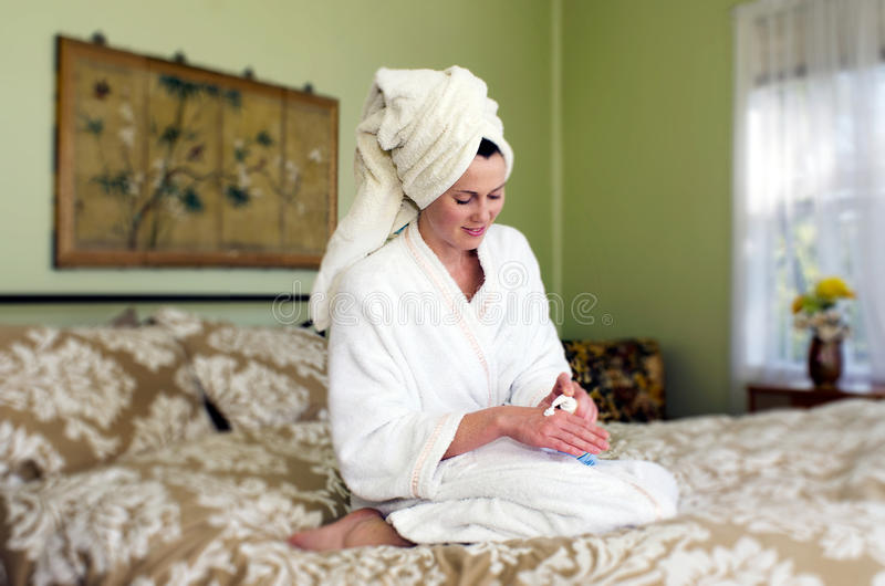 Young woman applies moisturiser to her skin stock photos