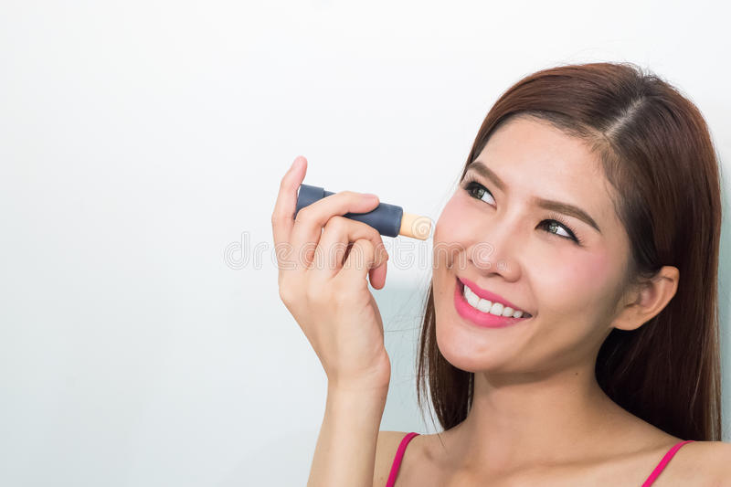 Young woman apply concealer under the eye. Close-up portrait of beautiful young woman model with perfect toned skin. Concealer under eyes stock image