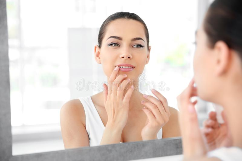 Young woman applying balm on her lips near mirror stock image