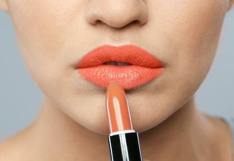 Young woman applying beautiful lipstick on gray, closeup royalty free stock photo