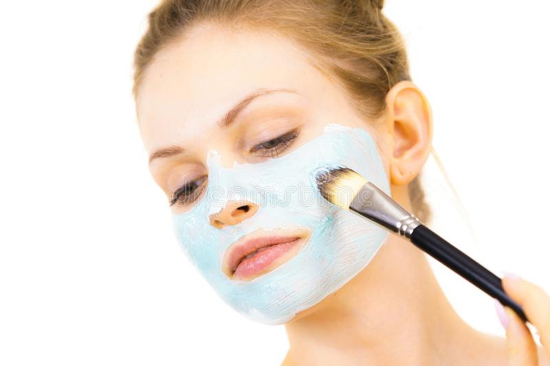 Girl apply green mud mask to face. Young woman applying with brush green mud mask to face, on white. Teen girl taking care of oily skin, purifying the pores royalty free stock images
