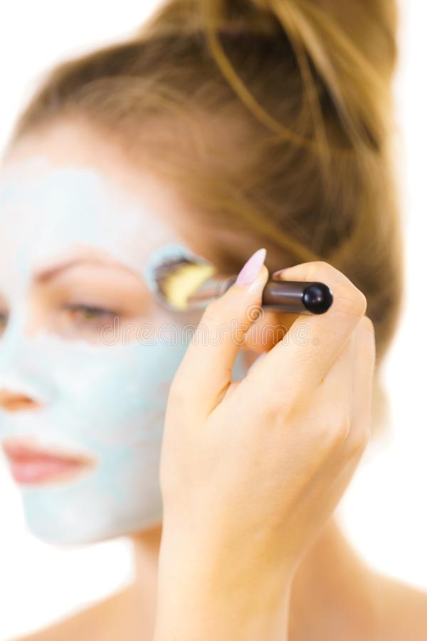 Girl apply green mud mask to face. Young woman applying with brush green mud mask to face, on white. Teen girl taking care of oily skin, purifying the pores royalty free stock photography