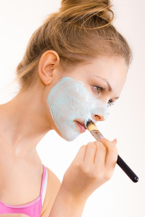Girl apply green mud mask to face. Young woman applying with brush green mud mask to face, on white. Teen girl taking care of oily skin, purifying the pores royalty free stock photos