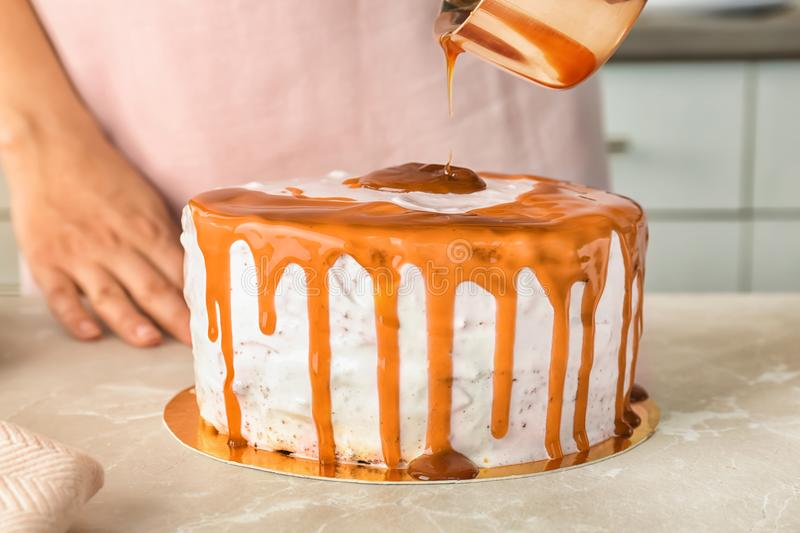 Young woman applying caramel sauce. Onto delicious homemade cake at table stock photography