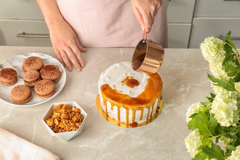 Young woman applying caramel sauce. Onto delicious homemade cake at table stock photos