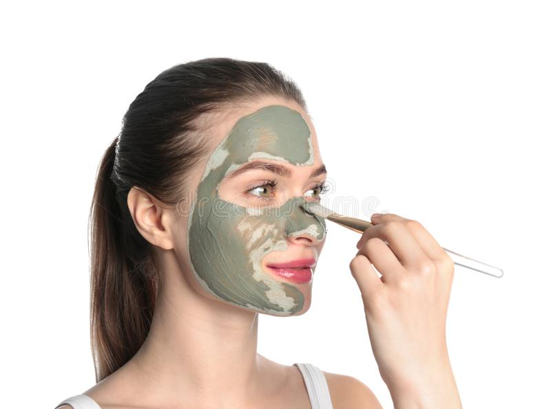 Young woman applying clay mask on her face. Skin care royalty free stock photo
