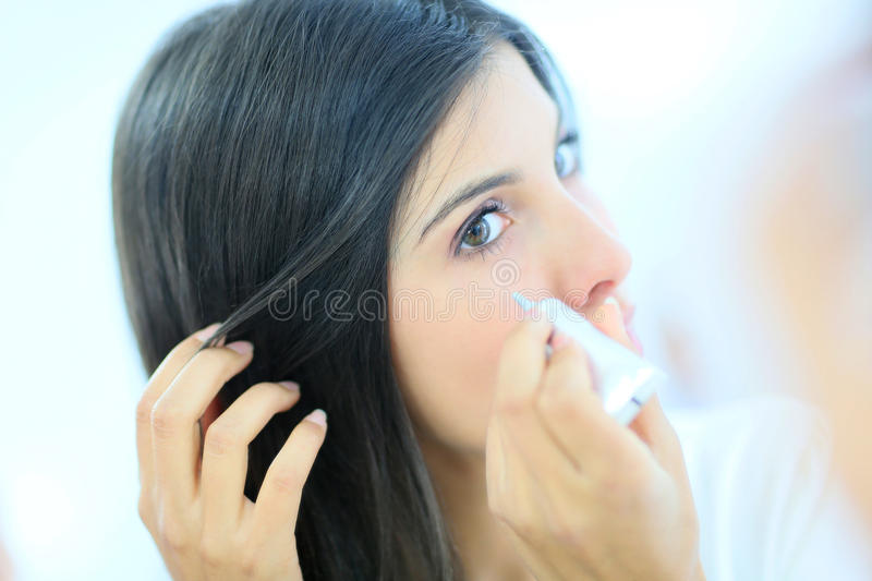 Young woman applying concealer. Beautiful brunette woman applying concealer stock image