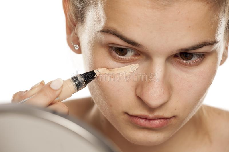 Woman applying concealer. Young woman applying concealer under her eyes on a white background stock photos