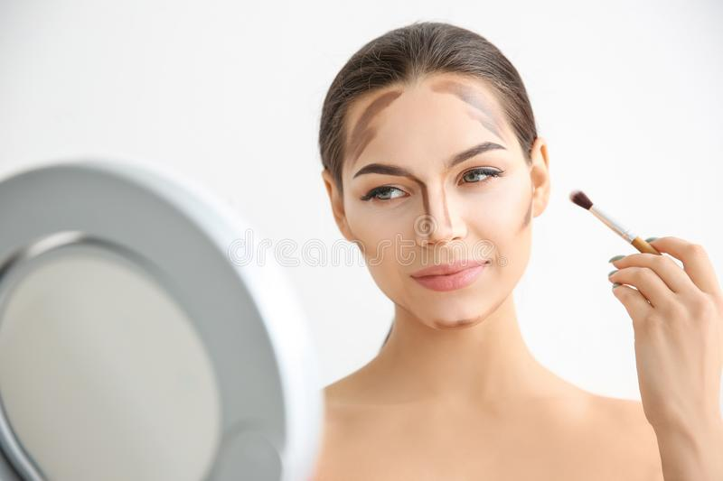 Young woman applying contouring lines stock images